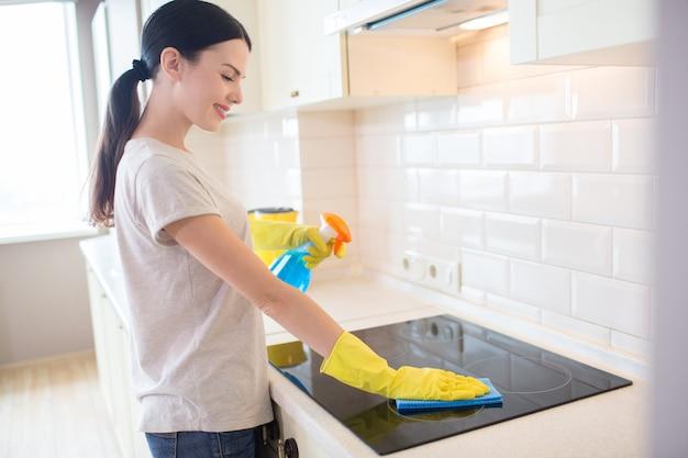 Uma morena agradável e positiva fica na frente do fogão e o limpa com um pano. ela também segura spray líquido azul na mão esquerda. menina usa luvas amarelas.