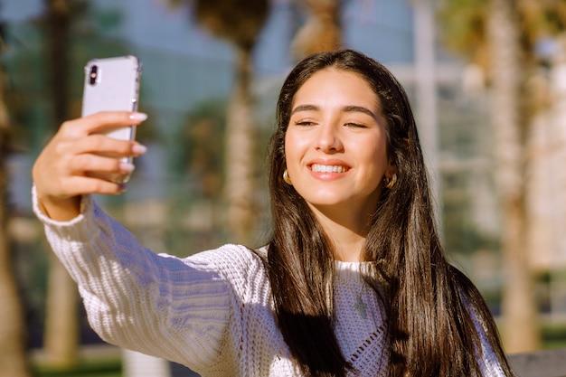Uma morena alegre com um sorriso largo, fazendo um selfie