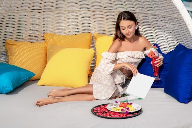 Uma morena bonita senta-se em um sofá com um coquetel vermelho na mão e seleciona bebidas ou alimentos tropicais no menu. viajar para países quentes. descanso e relaxamento