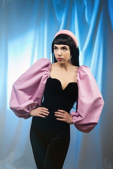 Uma morena chique glamour em uma blusa com mangas volumosas rosa da moda em um estilo retrô em um fundo de raios neon. estilo glamoroso.