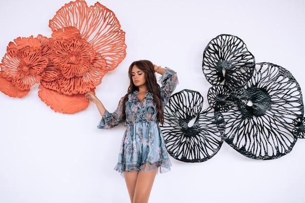Uma morena deslumbrante com cabelos ondulados em um vestido de renda na moda posa contra uma parede com decorações florais.