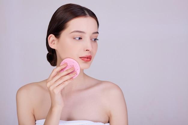 Uma morena gentil limpa a pele com uma esponja.