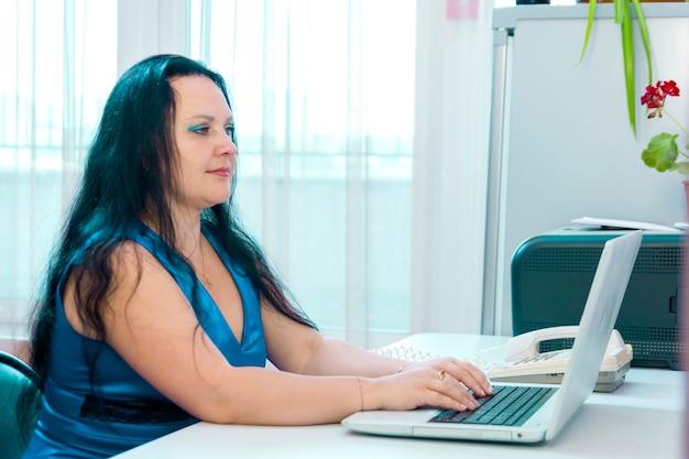 Uma morena judia em um escritório em casa, trabalhando em um laptop. foto horizontal