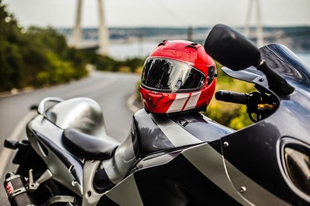Uma motocicleta preta cinza e um capacete vermelho.