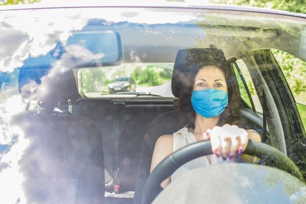 Uma motorista adulta com máscara cirúrgica protetora sentada no carro, olhando para a câmera