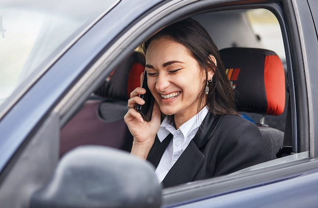 Uma motorista de mulher usando seu telefone celular enquanto dirige