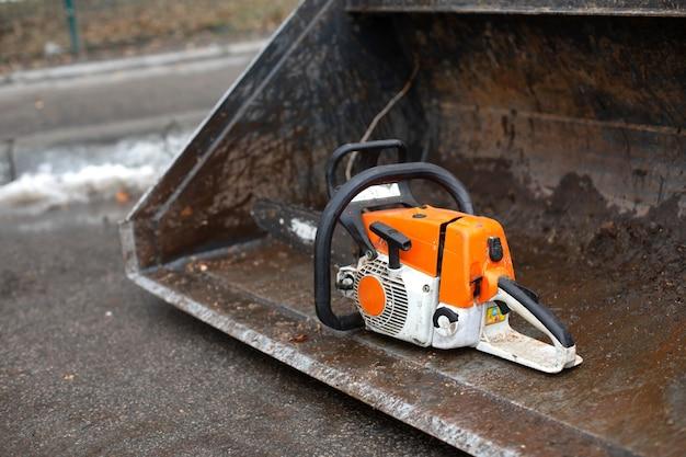 Uma motosserra está no balde do trator. trabalhadores cortam galhos de árvores