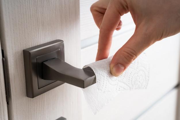 Uma mulher abre a porta com um guardanapo descartável. o conceito - cumprimento das regras de higiene, combate à epidemia de coronavírus