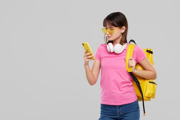 Uma mulher adolescente asiática em copos em forma de coração tem um telefone celular nas mãos. nova publicidade de gadgets