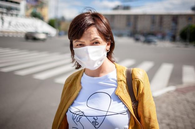 Uma mulher adulta bonita com roupas casuais e uma bolsa com uma máscara protetora no rosto está parada na estrada com carros que passam
