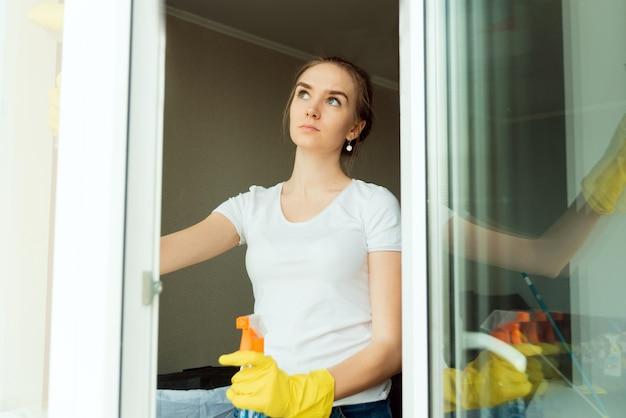 Uma mulher adulta bonita, trabalhadora de uma empresa de limpeza limpa as janelas de plástico de uma casa