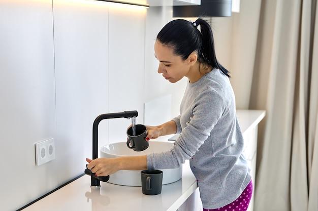 Uma mulher adulta branca despeja água na caneca da torneira da cozinha
