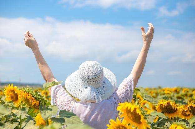 Uma mulher adulta com um chapéu branco esticou os braços para o céu, em um campo de girassóis
