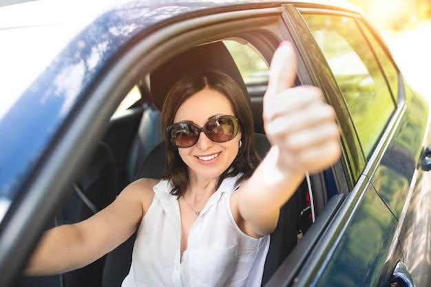 Uma mulher adulta de aparência inteligente colocou a mão para fora da janela do carro e ergueu os polegares