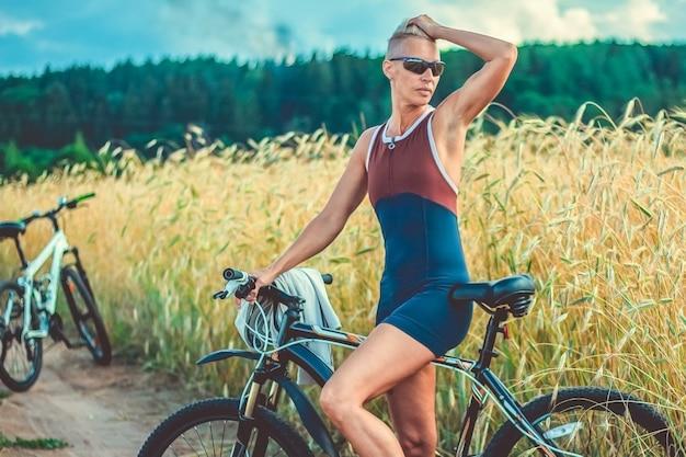 Uma mulher adulta de bicicleta, na margem de um lago. para qualquer propósito.