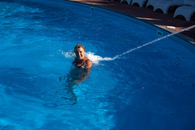 Uma mulher adulta e sorridente faz uma viagem de hidromassagem nas costas e pescoço com um jato d'água na piscina do spa.