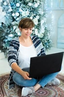 Uma mulher adulta se senta perto de uma árvore de natal com um laptop e sorri. cores azuis. compras online, comunicação.