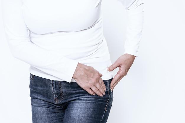 Uma mulher adulta tem um quadril dolorido no quarto branco.