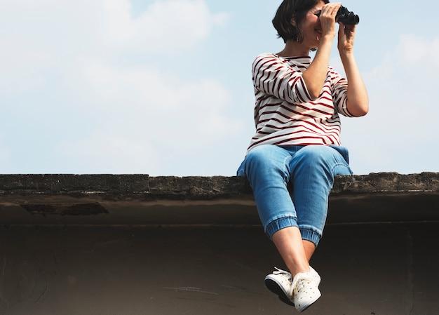 Uma mulher adulta usando binóculo e olhando para o céu