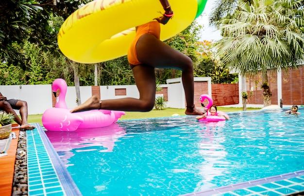 Uma mulher africana pulando na piscina com bóia inflável e aproveitando o horário de verão