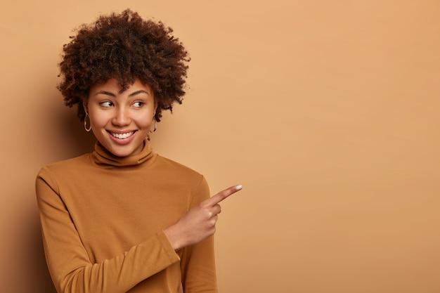 Uma mulher afro-americana alegre e satisfeita indica à parte, promove mercadorias, sorri com alegria, usa uma blusa de gola olímpica marrom, posa contra uma parede marrom. conceito de publicidade. coisas boas isso. olha lá