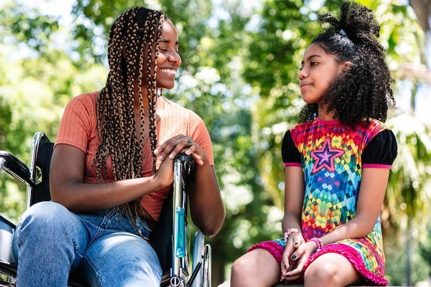 Uma mulher afro-americana em uma cadeira de rodas, curtindo um dia no parque e se divertindo com a filha