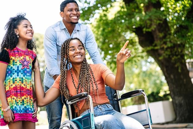 Uma mulher afro-americana em uma cadeira de rodas, desfrutando de um passeio ao ar livre com a filha e o marido.