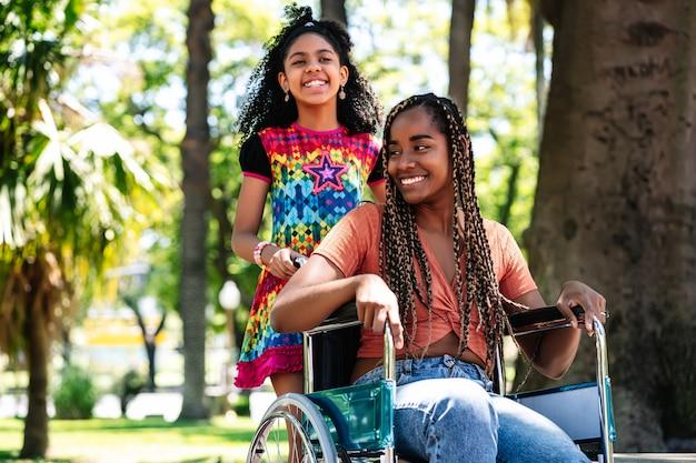 Uma mulher afro-americana em uma cadeira de rodas, desfrutando de um passeio no parque com a filha