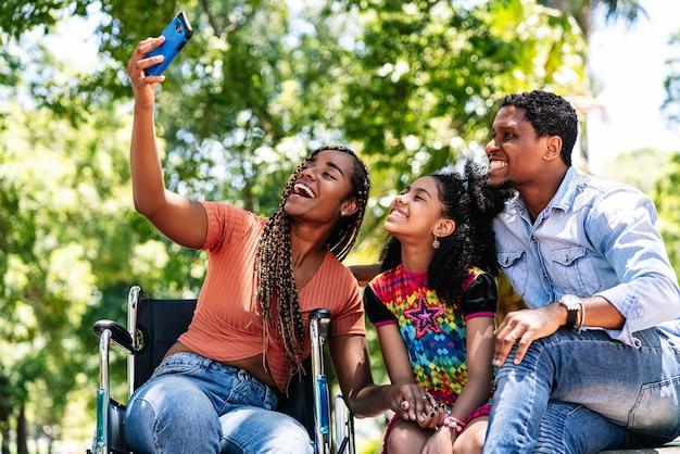Uma mulher afro-americana em uma cadeira de rodas tirando uma selfie com a família com um telefone celular enquanto desfruta de um dia no parque