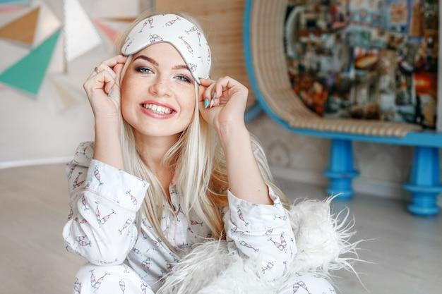 Uma mulher alegre ri e senta-se de pijama pela manhã. sl