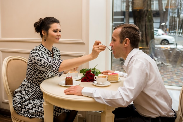 Uma mulher alimenta um homem com uma colher em uma mesa em um café