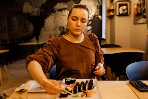 Uma mulher almoça em um café, segura os chopsticks para comer sushi.