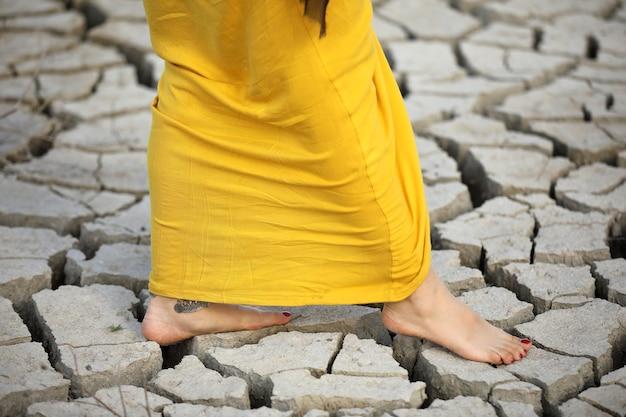 Uma mulher anda descalça no chão seco.