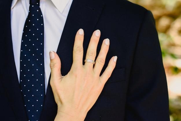 Uma mulher apaixonada se inclina com a mão no peito do homem vestido de terno elegante.