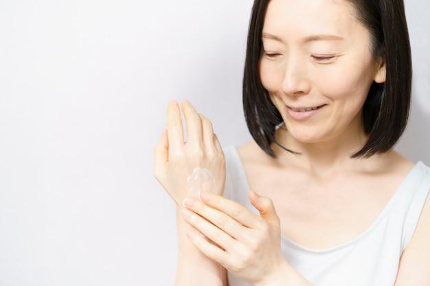 Uma mulher aplicando creme nas costas da mão