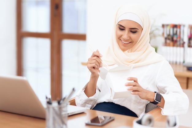 Uma mulher árabe em um hijab está almoçando.