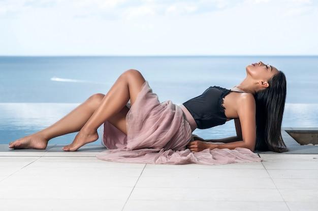 Uma mulher asiática bonita com belas pernas finas e olhos fechados posa na beira da piscina infinita. foto de publicidade na moda