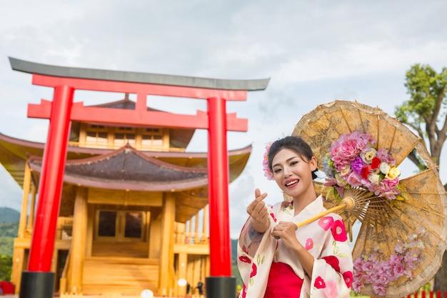 Uma mulher asiática bonita que desgasta um quimono japonês, conceito tradicional do vestido.