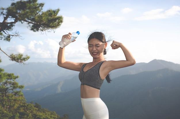 Uma mulher asiática bonita que meditating e que exercita na parte superior da montanha.