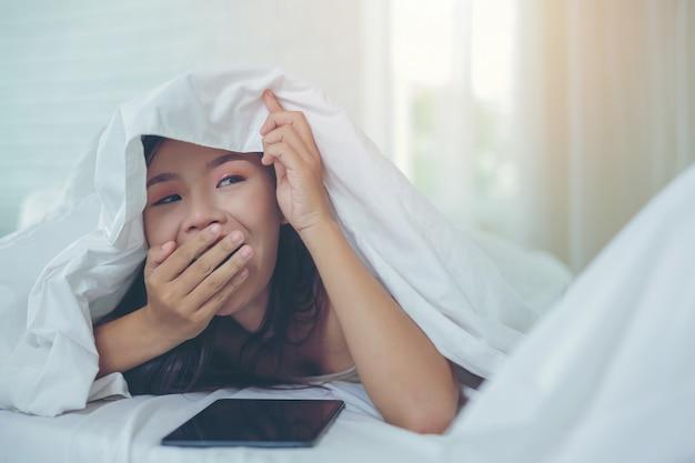 Uma mulher asiática bonita relaxa e trabalha com um computador portátil, lendo em casa.