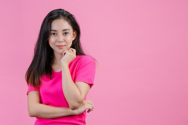 Uma mulher asiática branca coloca a mão esquerda contra o queixo em um rosa.