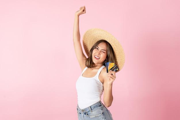 Uma mulher asiática com um vestido de verão, segurando um cartão de crédito e levantando a mão