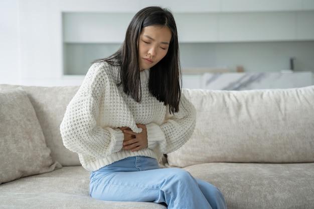 Uma mulher asiática com uma blusa branca está sentada no sofá e sente uma forte dor abdominal que é