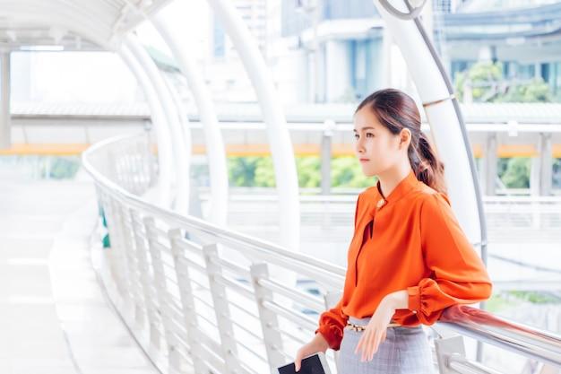 Uma mulher asiática com uma camisa laranja de mangas compridas está encostada em uma grade. Foto Premium