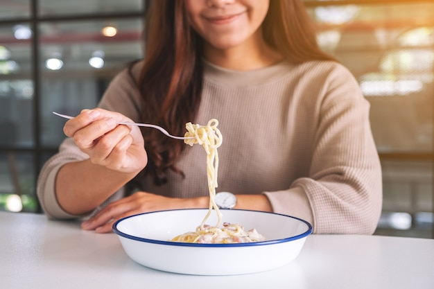 Uma mulher asiática comendo espaguete à carbonara