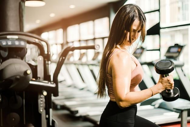 Uma mulher asiática de cabelos castanhos levantando halteres e olhando para os músculos do braço em uma academia de ginástica.
