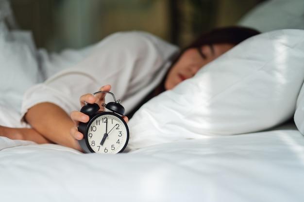 Uma mulher asiática desligar um despertador enquanto dorme em uma cama aconchegante branca de manhã