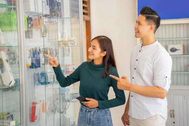 Uma mulher asiática e um homem apontando para uma vitrine de vidro
