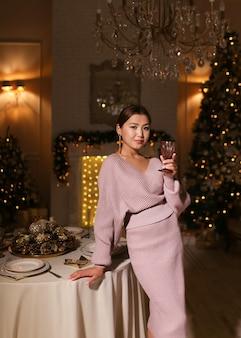 Uma mulher asiática em um vestido elegante de luxo está à mesa de jantar com uma taça de vinho na mão