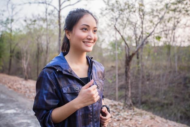 Uma mulher asiática está correndo e sorrindo feliz em relaxar e ela usa um relógio de fitness ou esporte.